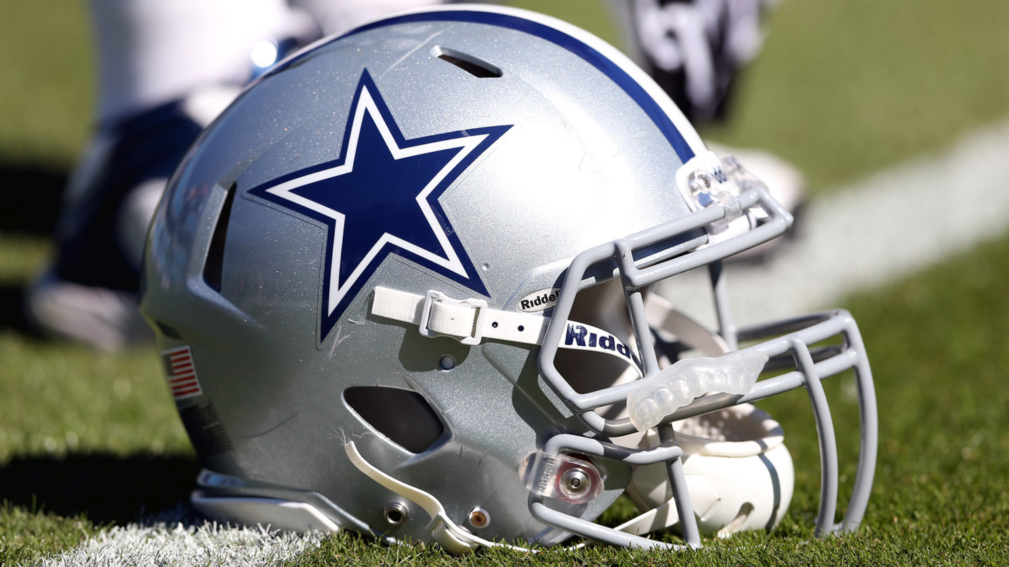 A Dallas Cowboys helmet sits along the side of the football field during a game.