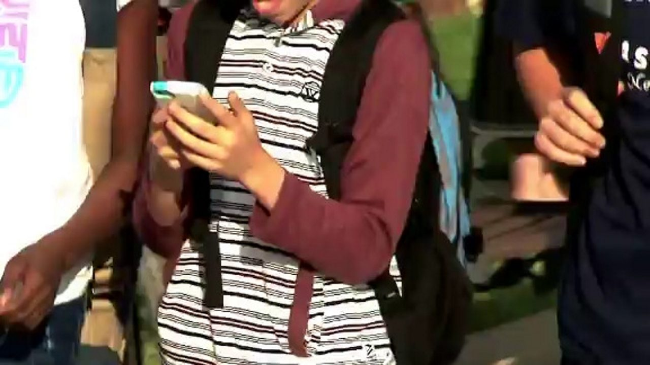 A teenager on a cellphone alongside other kids leaving school.