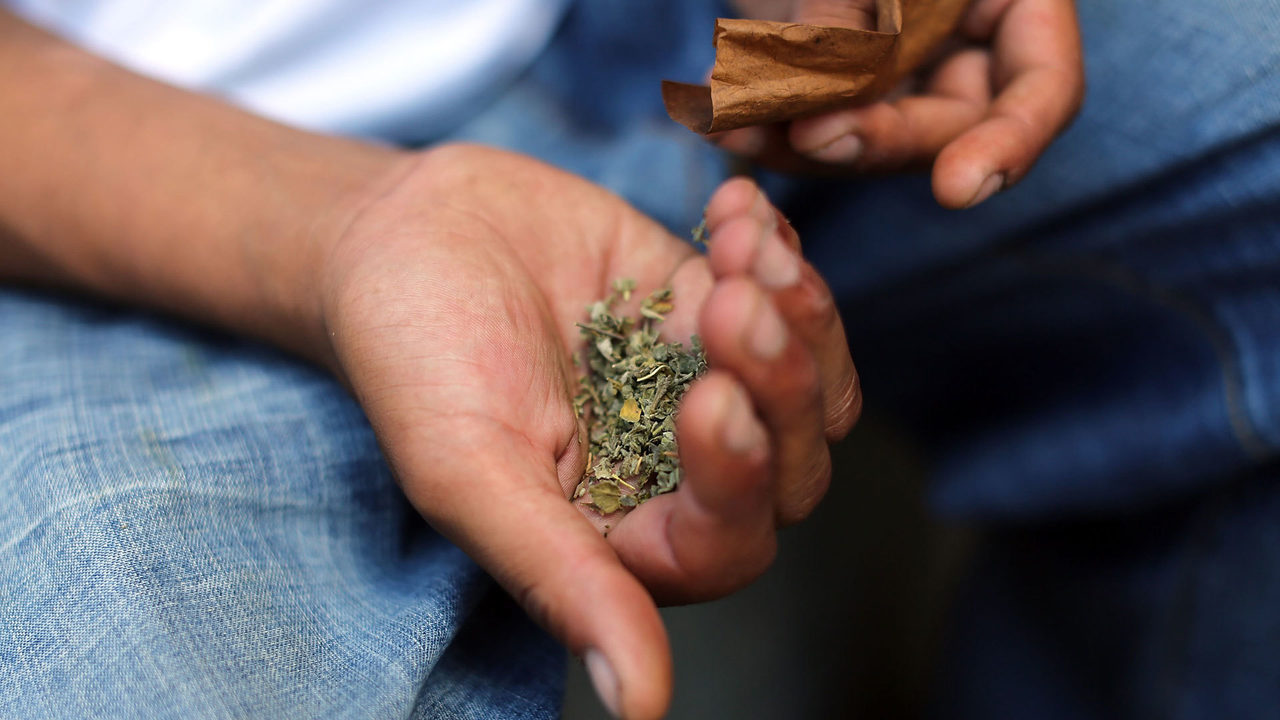 A man holds a small amount of marijuana in his hand.