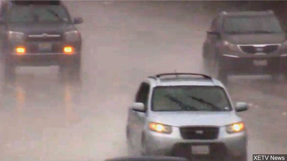 Motorists navigate wet roads in a pouring rain.