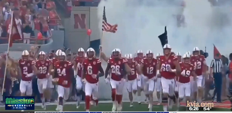 The Nebraska Cornhuskers football team runs onto the field during a game last season.