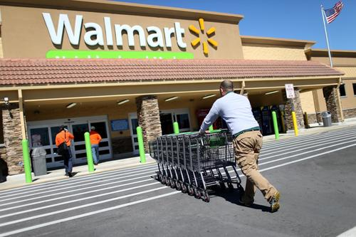 An employee pushes shopping carts from the packing lot back to a Walmart store in this file photo.