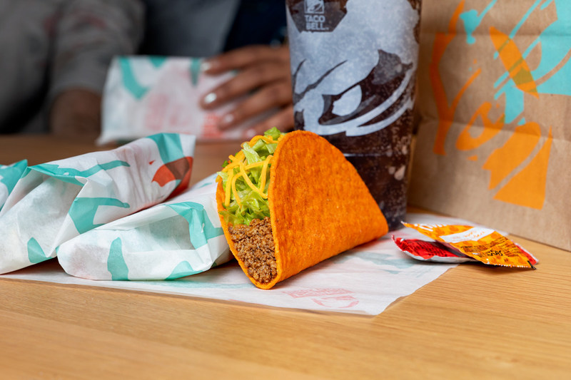 A customer enjoys Taco Bell tacos along with a soft drink.