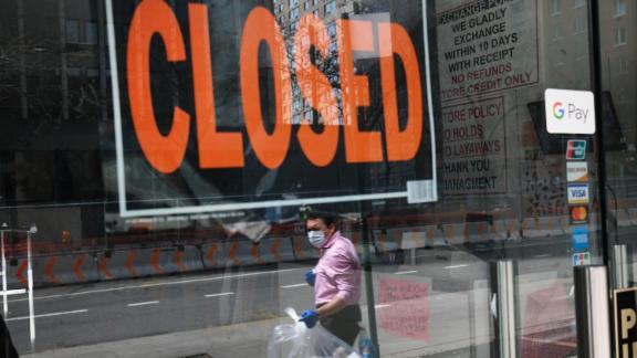 A person walks by a business with a closed sign in the window.