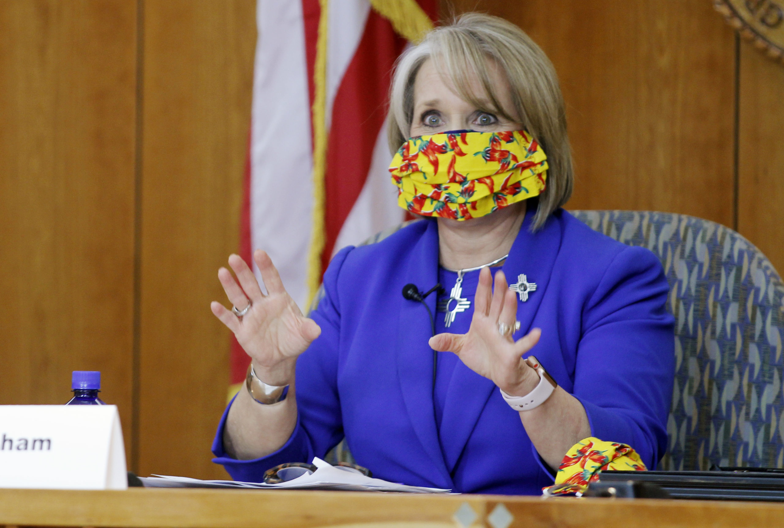 New Mexico Gov. Michelle Lujan Grisham delivers a press conference wearing a face mask covering.