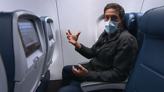 An air traveler wearing a mask takes his seat after boarding a plane.