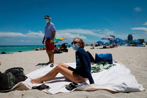 Californians wear face masks at the beach.