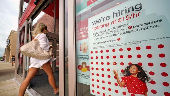 A hiring sign is posted in a storefront window.