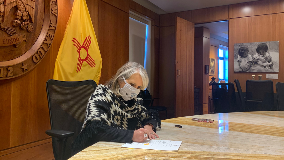 New Mexico Gov. Michelle Lujan Grisham signs a measure into law.