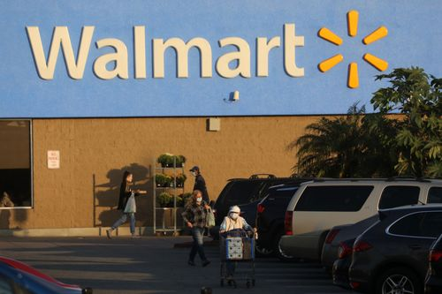 Customers head for their cars after shopping at a Walmart store.