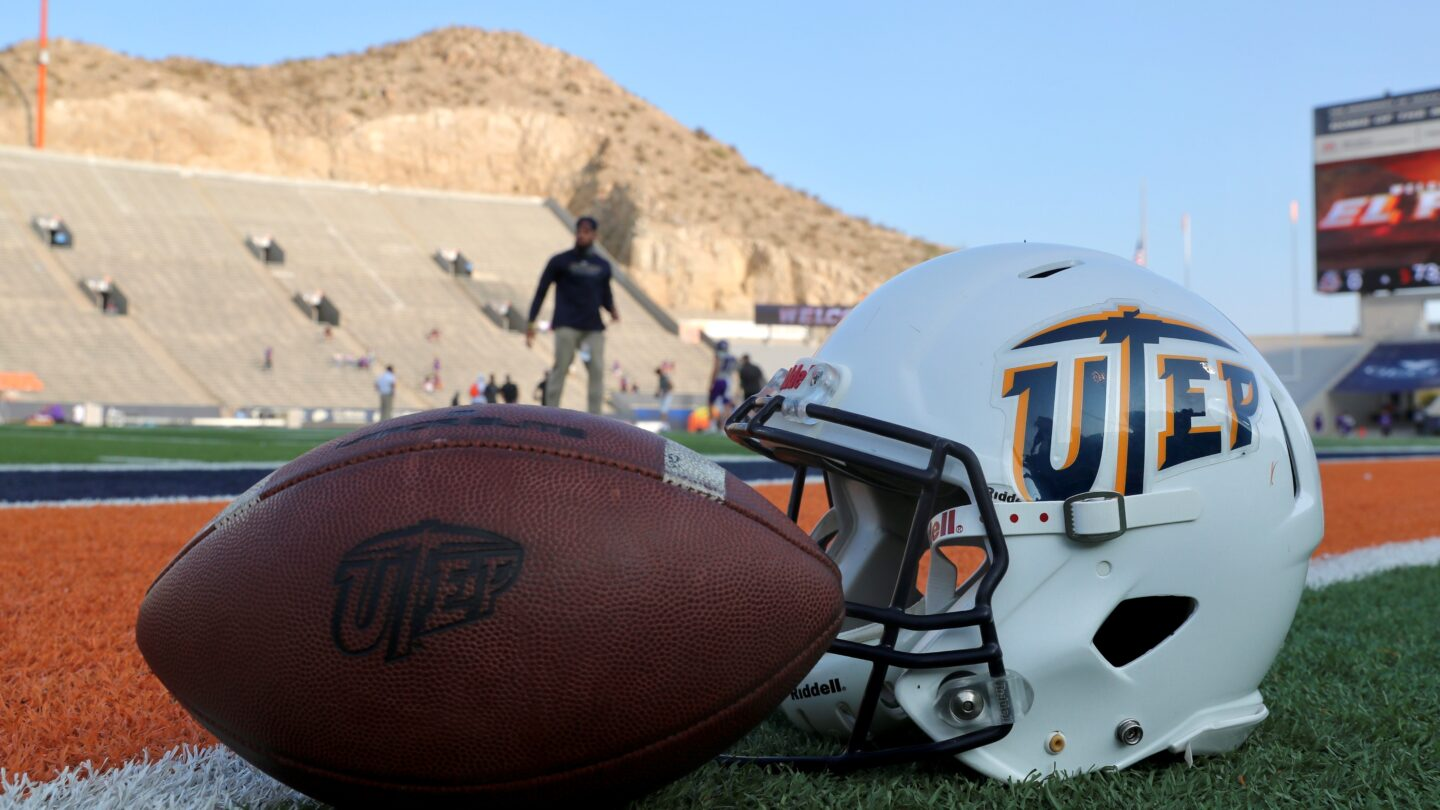 A UTEP football and helmet sits on the field at the Sun Bowl stadium.