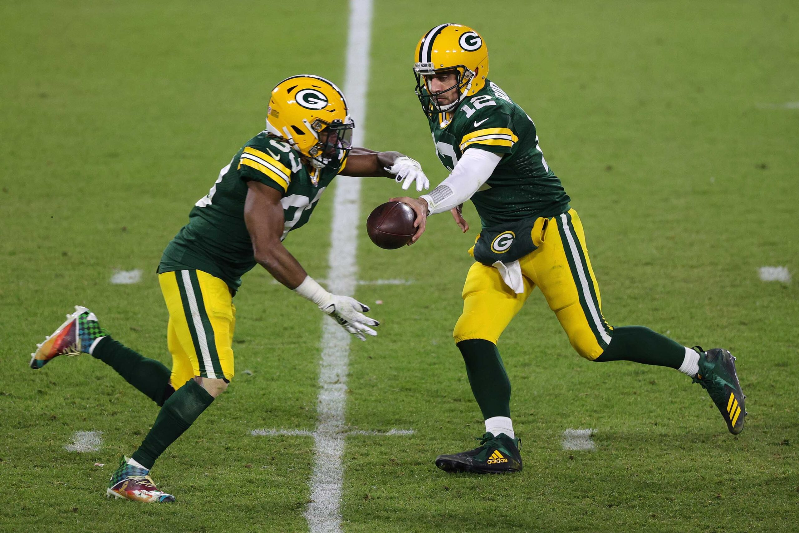 Aaron Rodgers #12 of the Green Bay Packers hands the ball to Aaron Jones #33.