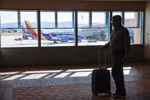 A man waits with his luggage in an airport terminal for a Southwest Airlines flight.