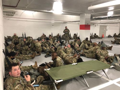 National Guard troops rest in a parking garage near the U.S. Capitol.
