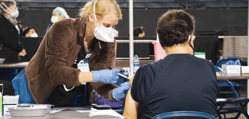 A nurse administers a Covid-19 vaccine at University Medical Center's vaccination hub at the El Paso County Coliseum.