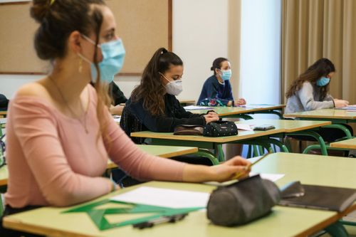 Students wear masks in a socially-distanced school classroom.