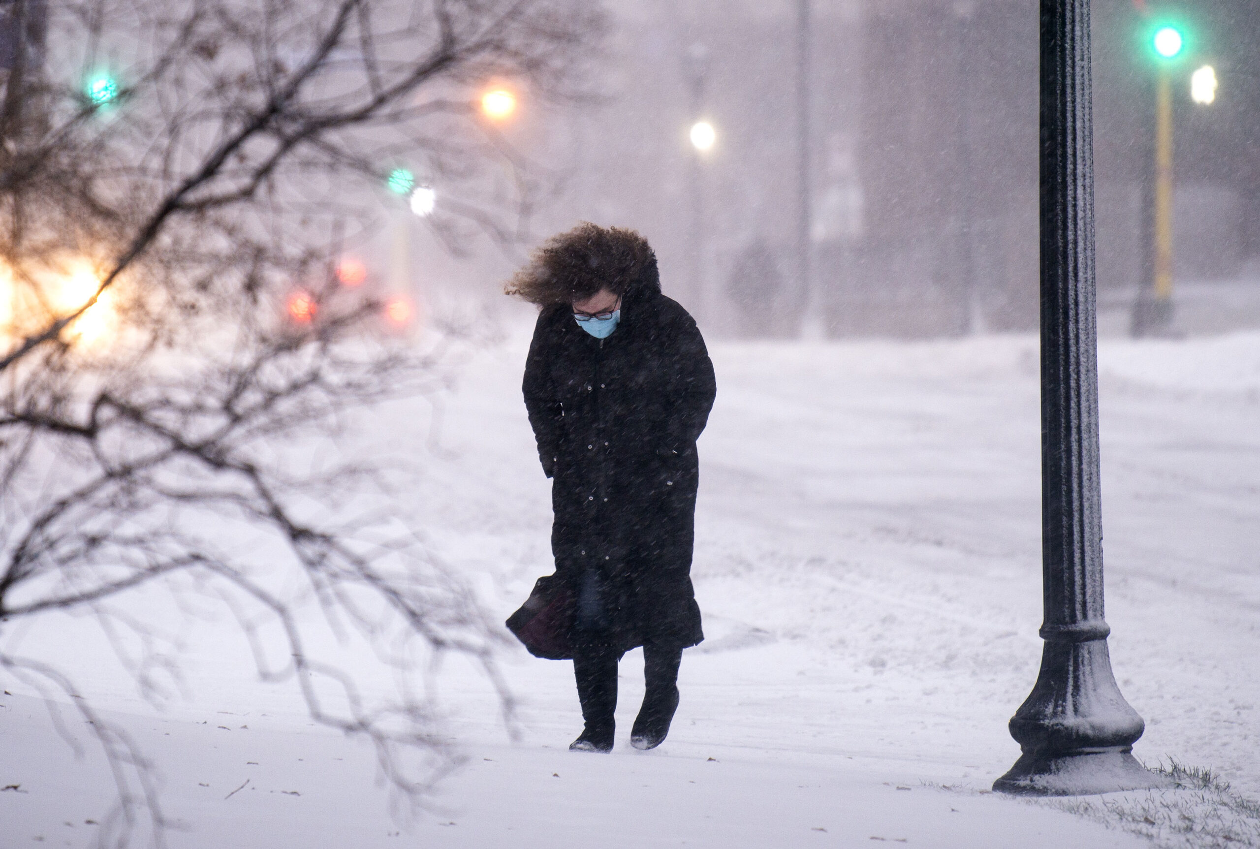 Wind blows and snow falls as a woman walks through downtown  Minneapolis.