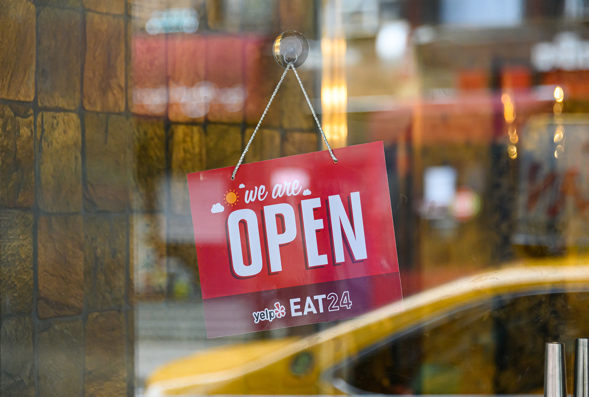 A 'We Are Open' sign is seen outside a restaurant.