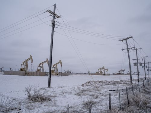 Oil rigs and power lines amid the snow in Odessa, Texas.