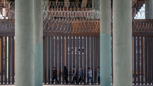 Undocumented immigrants walk along the U.S.-Mexico border wall after they ran across the shallow Rio Grande into El Paso.
