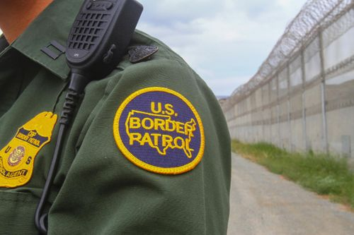 A U.S. Border Patrol agent stands near a section of border fence.