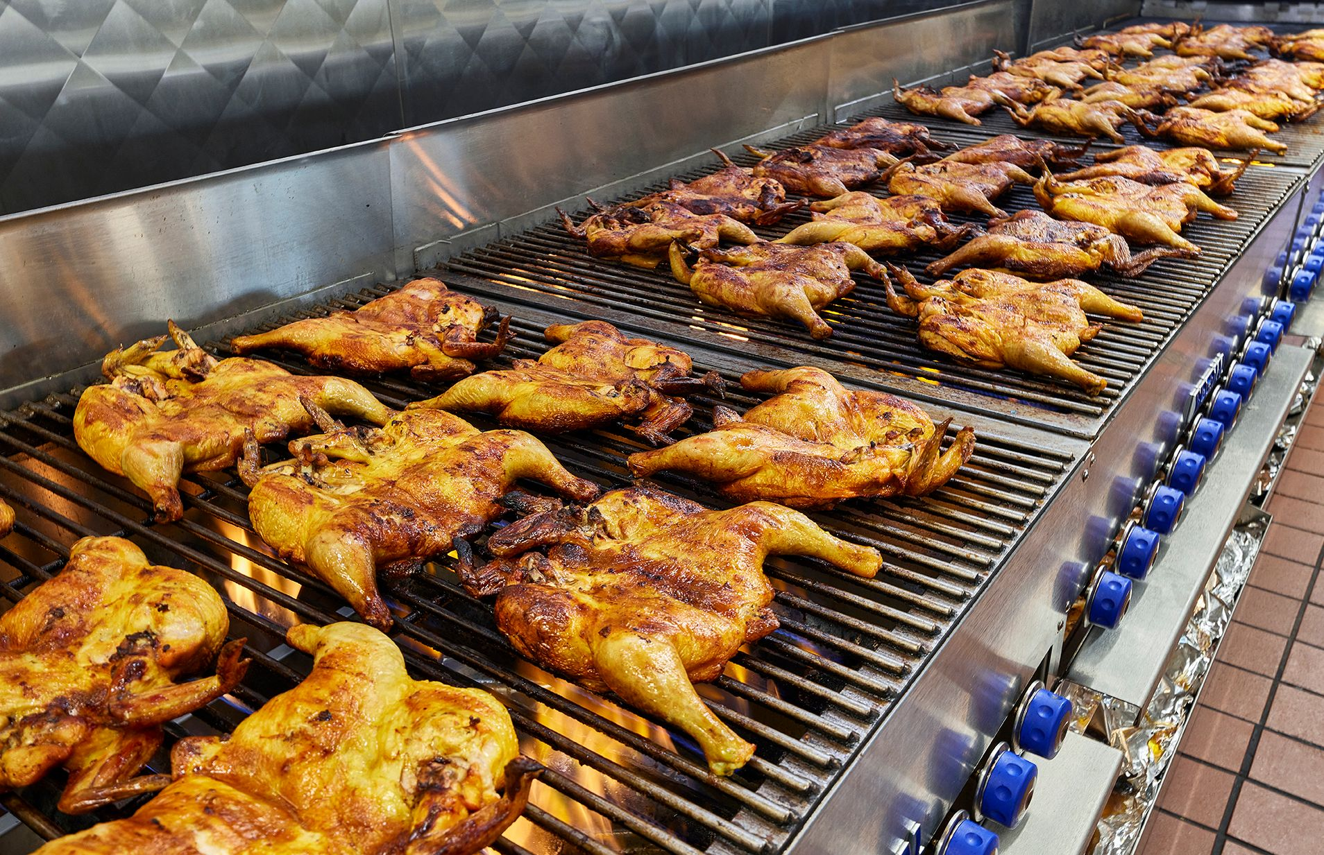 Chicken on the grill in the kitchen at an El Pollo Loco restaurant.
