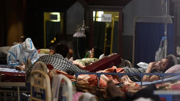 Coronavirus patients rest inside a banquet hall temporarily converted into a Covid-19 ward in New Delhi, India.