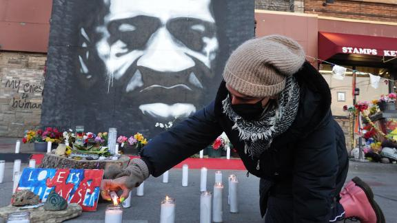 A man lights candles in front of a memorial for George Floyd.