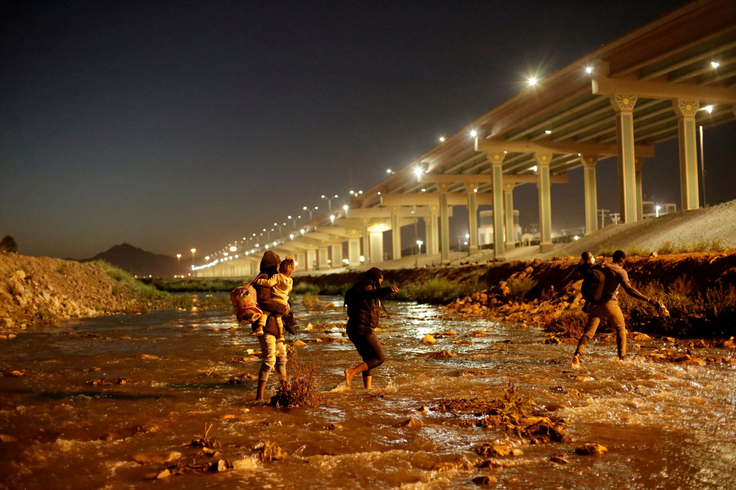 Migrants cross the Rio Bravo river to turn themselves in to U.S Border Patrol agents to request for asylum in El Paso, as seen from Ciudad Juarez.