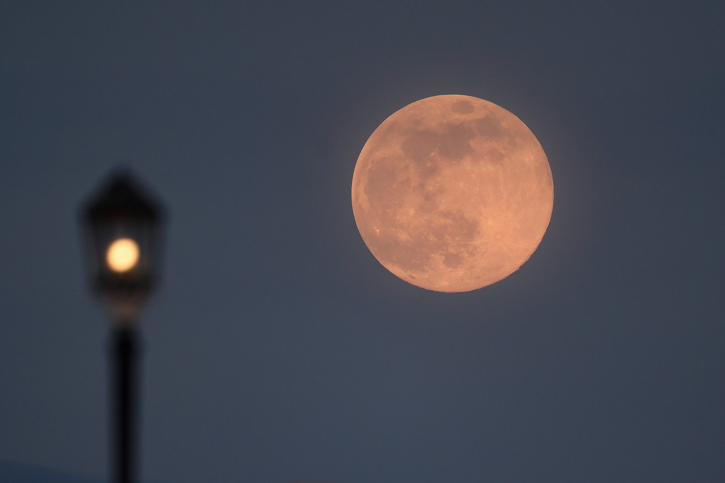 A pink supermoon rises over a pier in Worthing, United Kingdom in 2020.