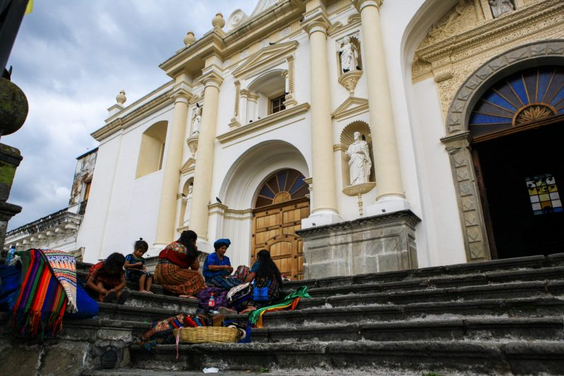 Indigenous women in Antigua, Guatemala, work on textiles that will be sold to tourists.