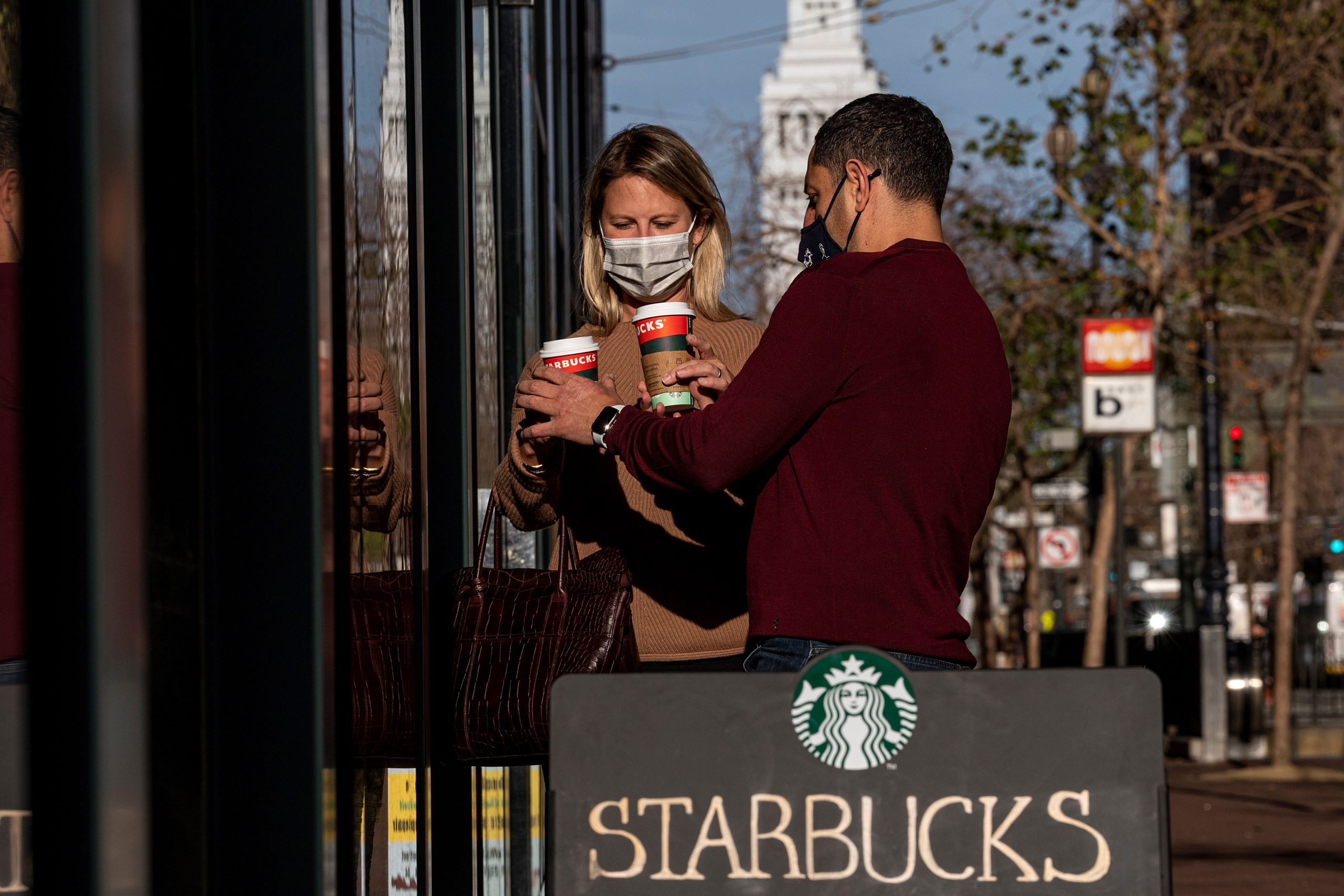 People wearing protective masks hold beverages outside a Starbucks coffee shop in San Francisco, California.