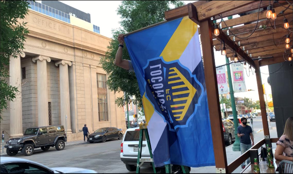 An El Paso Locomotive FC flag hangs on display in downtown.
