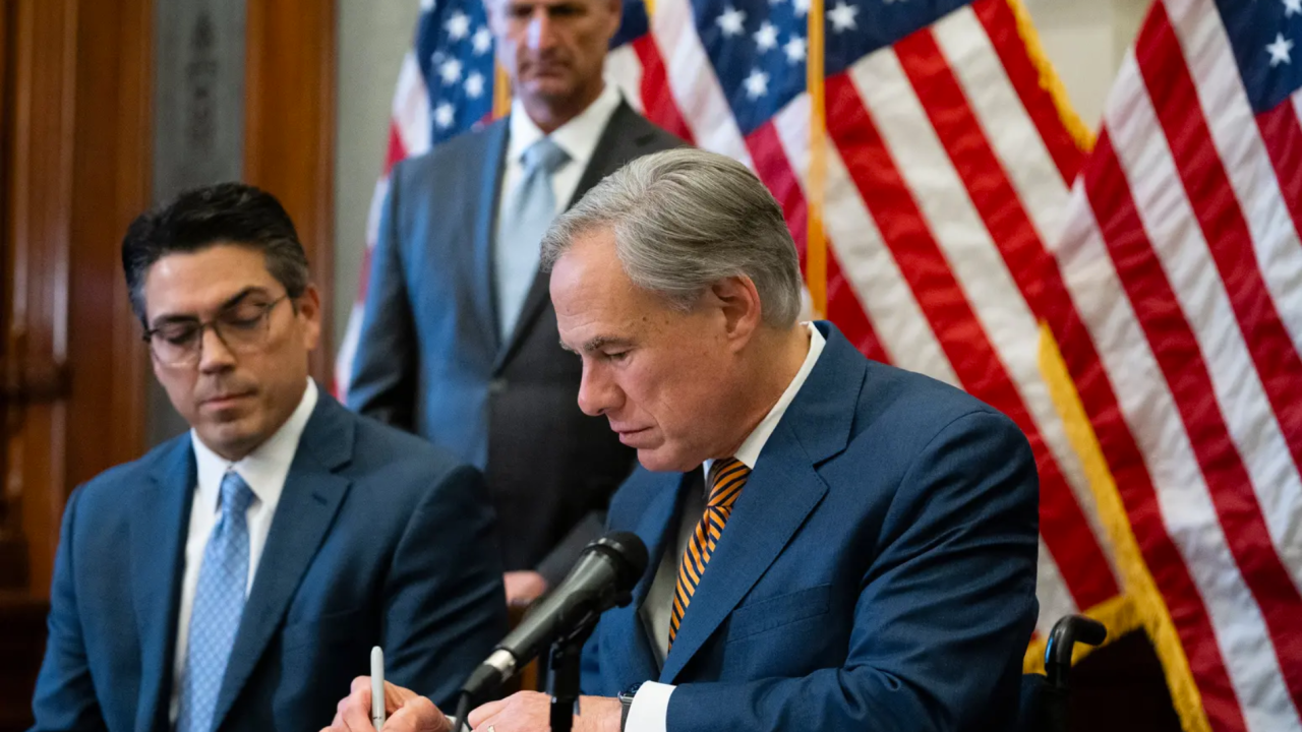 Gov. Greg Abbott signs a bill at the Texas Capitol.
