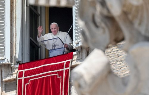 Pope Francis waves from a window overlooking St. Peter's Square in the Vatican during the weekly Angelus prayer followed by the recitation of the Regina Coeli on May 9.