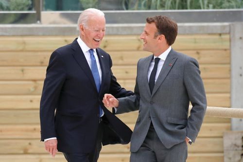 President Biden shakes hands with the president of France at the G7 Summit.