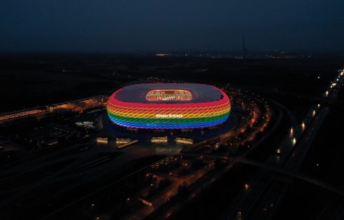 A drone image shows the Allianz Arena soccer stadium illuminated in rainbow colours during the Bundesliga match between FC Bayern Muenchen and TSG Hoffenheim on January 30 in Munich