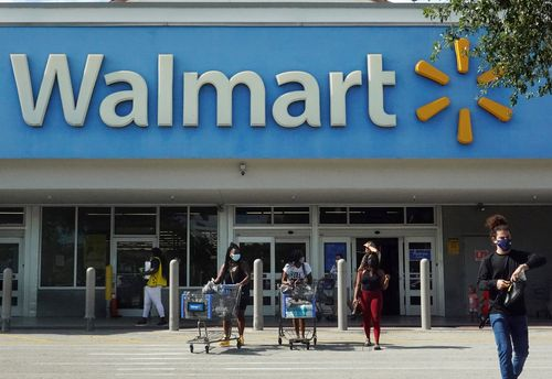Shoppers exit a Walmart store after making purchases.
