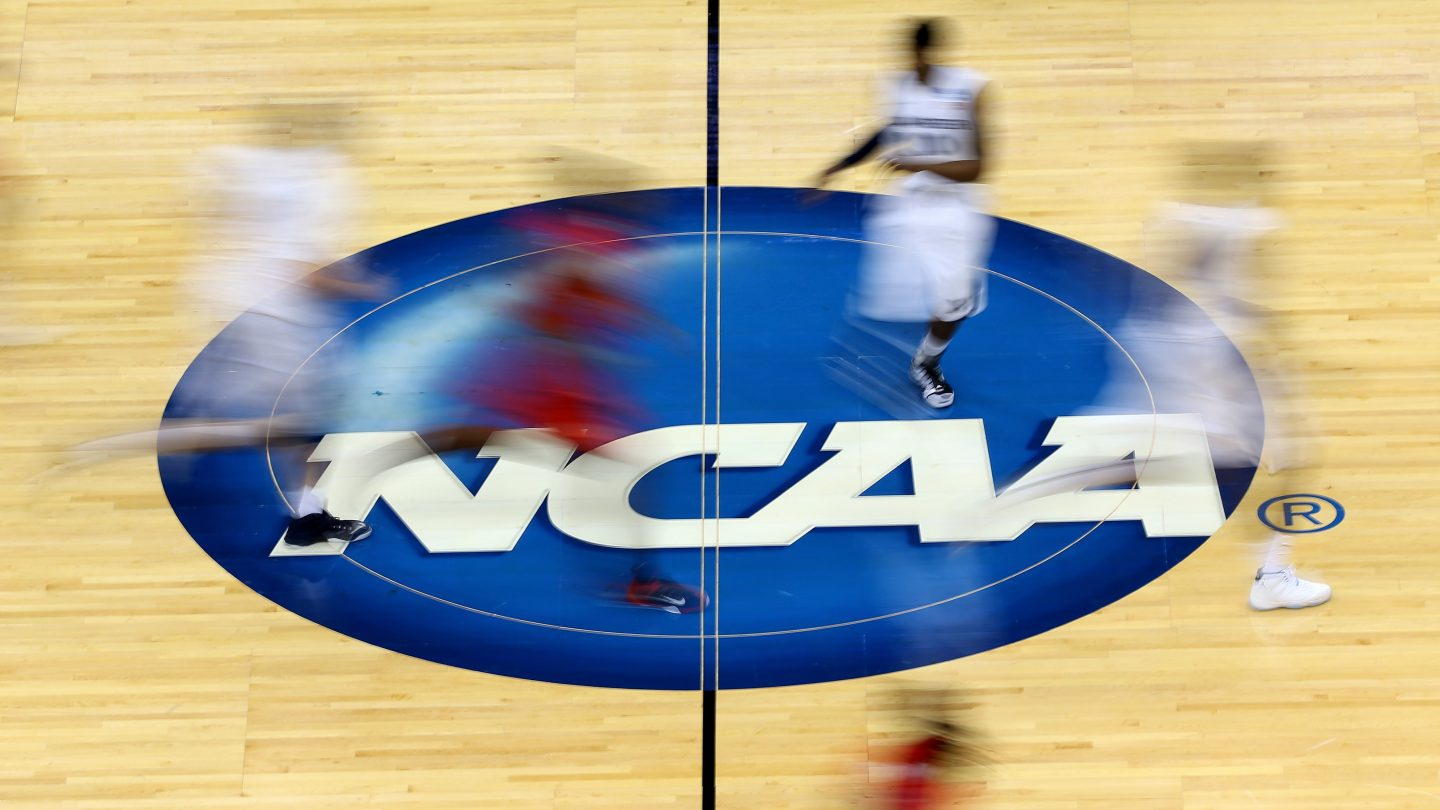 College basketball players run by the NCAA logo at mid-court during March Madness.