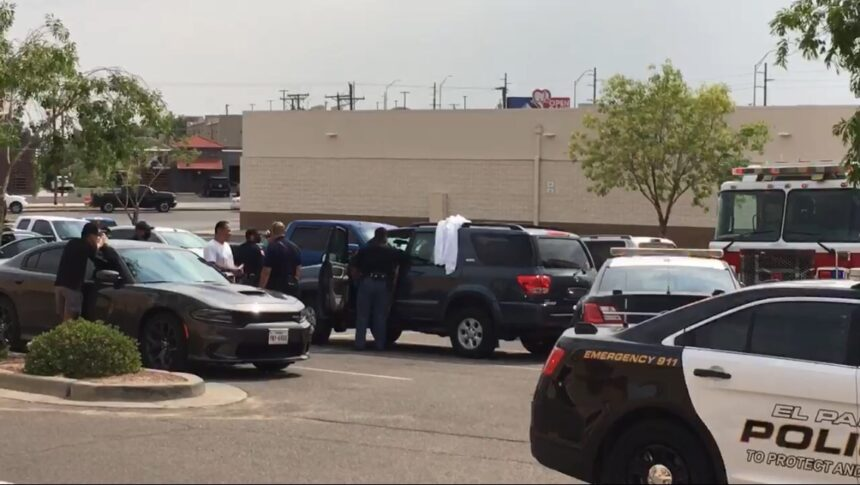 White sheet covers a vehicle containing the body of a woman in an east El Paso paring lot.