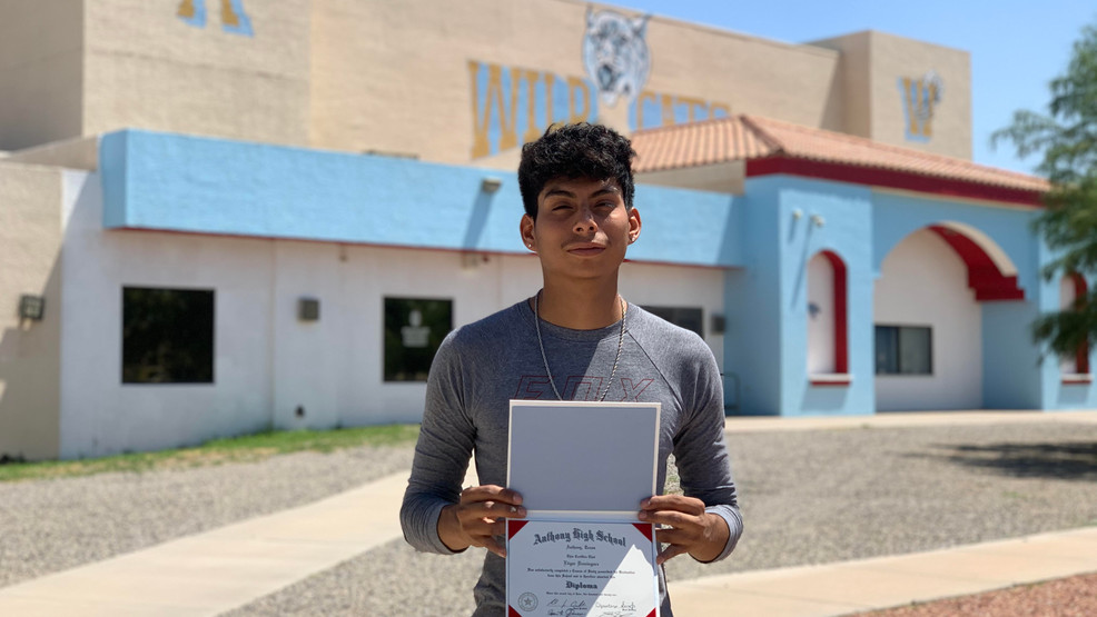 Edgar Dominguez shows his diploma as he stands in front of Anthony High School.