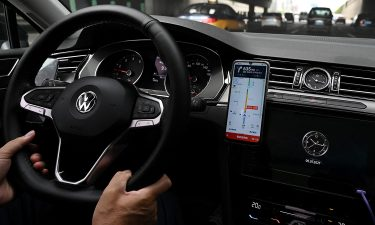 A driver uses the map on the Didi Chuxing ride-hailing app on his smartphone while driving on a street in Beijing on July 5. Shares in Didi crashed 20% after Chinese authorities opened an investigation into the ride-hailing giant that raised $4.4 billion last week in a massive IPO in New York.