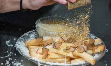 Chef Frederick Schoen-Kiewert applies 23-carat edible gold dust on top. as he prepares The Creme de la Creme Pommes Frites
