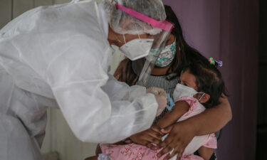 A mother in Brazil holds her daughter while a nurse gives her a flu vaccine.
