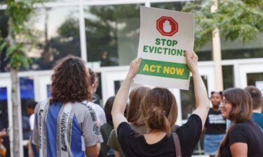 A woman holds a placard to stop evictions at a rally for housing reform.