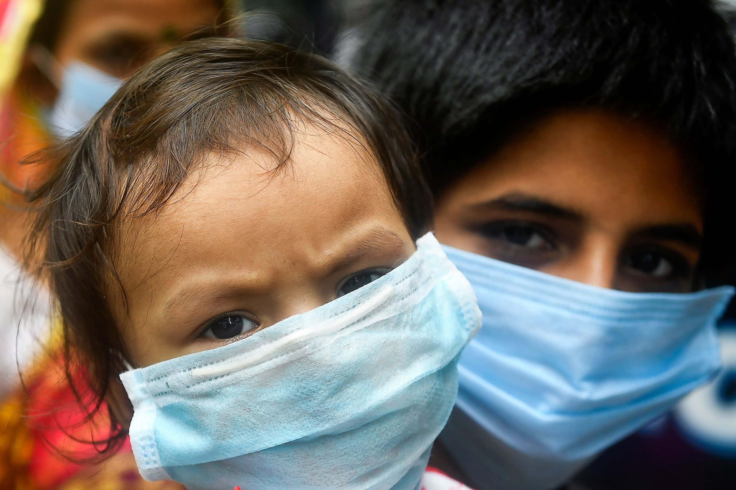 <i>DIBYANGSHU SARKAR/AFP/AFP via Getty Images</i><br/>Children wear facemasks and wait in a queue with others to take swab samples to test for the Covid-19 coronavirus