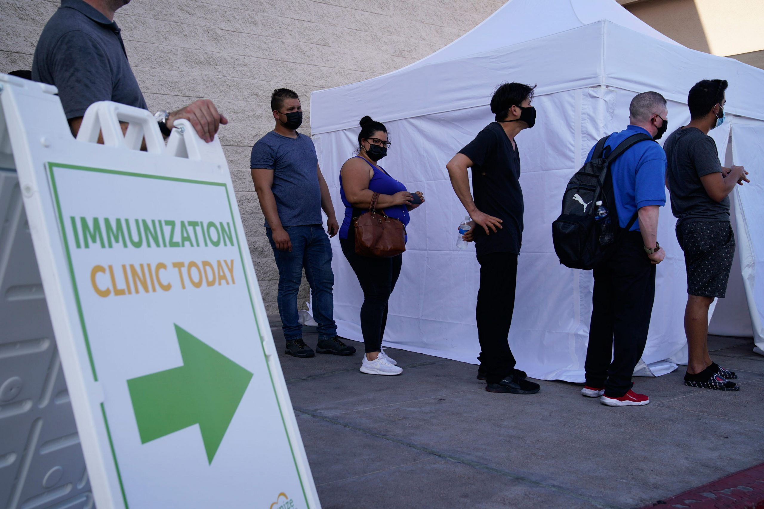 <i>John Locher/AP</i><br/>People wait in line for Covid-19 vaccinations at an event at La Bonita market