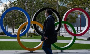 A man wearing a face mask walks in front of the Olympic Rings in Tokyo on March 11