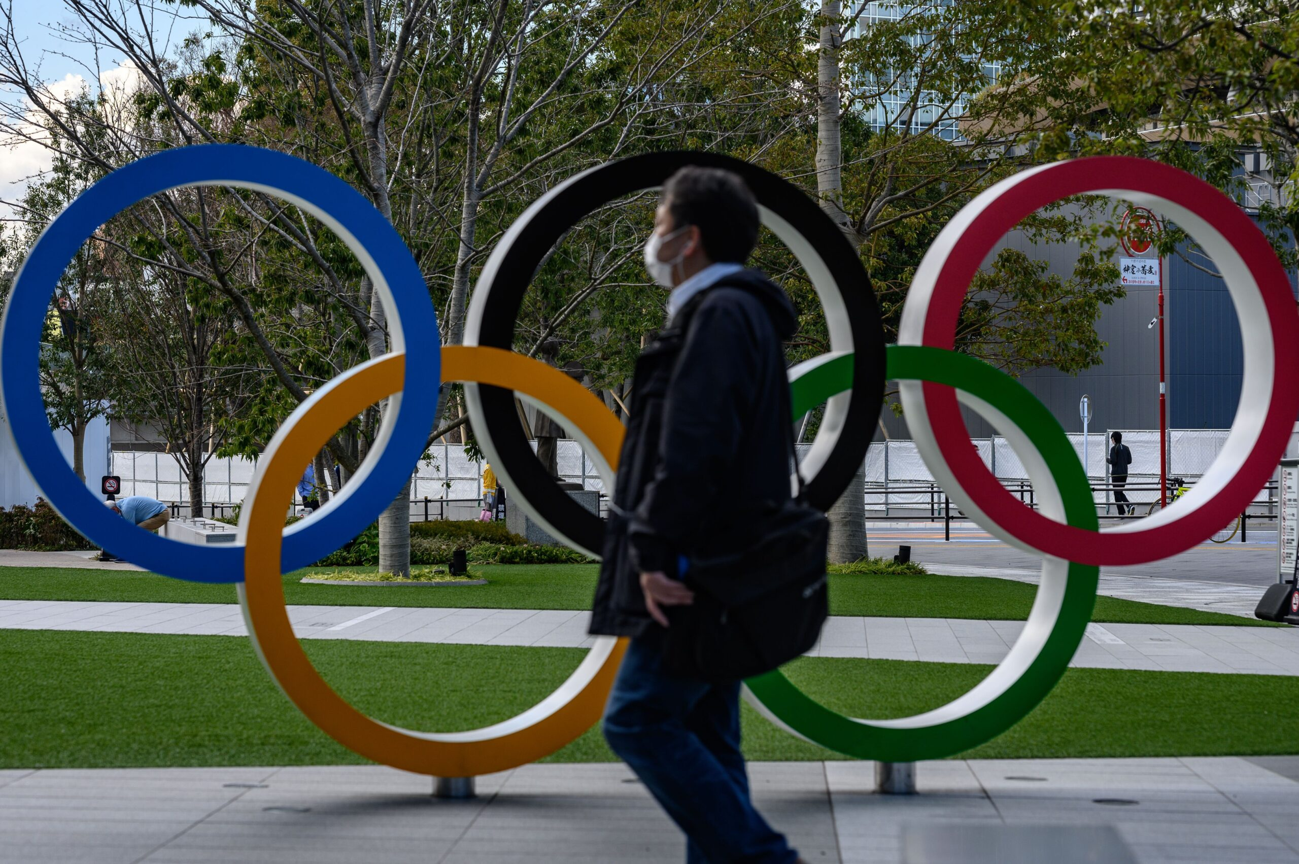 <i>PHILIP FONG/AFP/AFP via Getty Images</i><br/>A man wearing a face mask walks in front of the Olympic Rings in Tokyo.