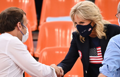 French President Emmanuel Macron and First Lady Jill Biden shake hands ahead of the women's first round 3x3 basketball match between the US and France.